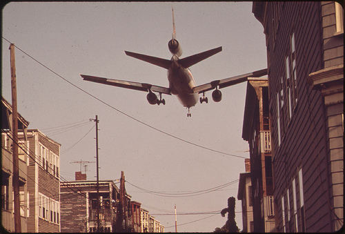 plane flies in low over houses to logan airport 1973