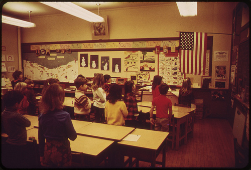 students in classroom recite pledge of allegiance to american flag